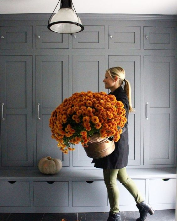 A blond girl carries a huge bucket of dark orange mums in front of a wall of gray cabinets