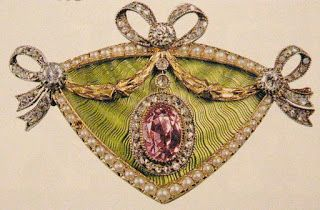 A beautiful chartreuse green enamel brooch bordered in seed pearls with three diamond bows and a golden garland.