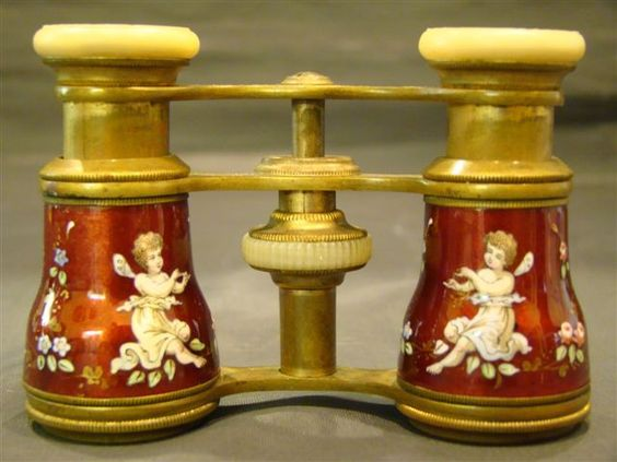 This gorgeous set of enamel decorated opera glasses features two cherubs or putti, one on each barrel. Enameled red roses and other flowers decoration extend around the entire body of the glasses. The background is a stunning ruby red. The metalwork is brass, with mother of pearl eyepieces. They are likely French, and date to the late 1800's. There are no markings or signature indicating their manufacturer. The mechanism properly extends and retracts.
