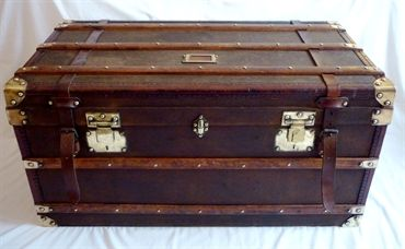A vintage French steamer trunk circa 1930. The trunk is fabric covered with wood bands, leather trim and brass detail. The interior is in good condition and retains it's original trays.