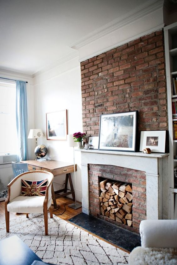 Union Jack pillow, exposed brick, wood-filled fireplace. I'm in love! A CUP OF JO: Our house tour