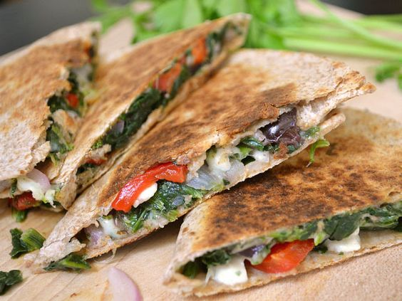 Mediterranean quesadillas filled with a mix of spinach, feta cheese, olives, tomatoes, and red onion.