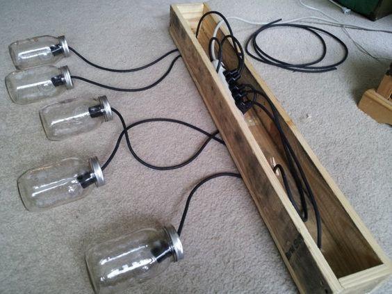 afin de fabriquer une suspension, on enfile les câbles avec douilles et les ampoules vissées dans des bocaux de verre