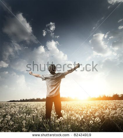 Young man standing on a meadow with raised hands and looking to a sky by Dudarev Mikhail, via Shutterstock