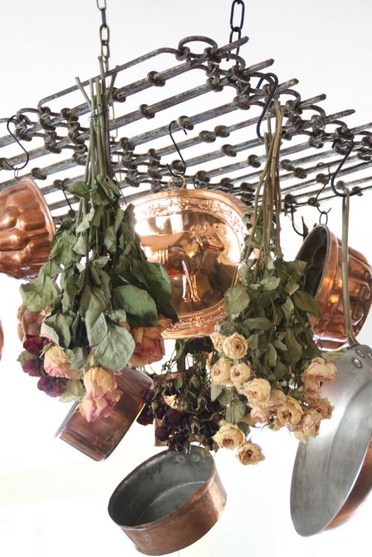 Warm Copper and Dried Roses hanging from a salvaged iron fence piece turned pot rack