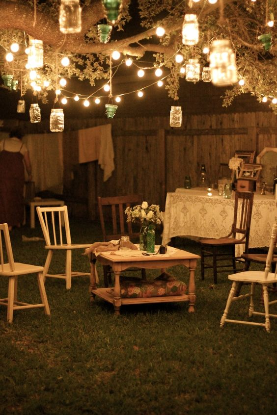 Garden party at night; lanterns hang from tree branches, and rustic furniture with flowers and lace tablecloths give a charming and relaxed feel.