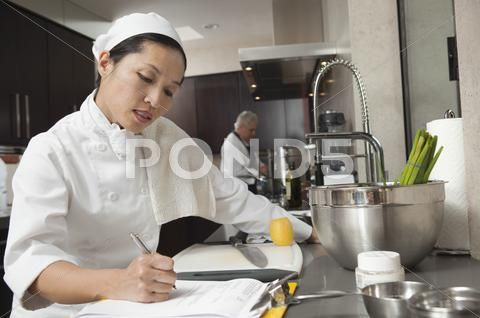 Photograph Female Chef Writing On Clipboard In Kitchen 32023967