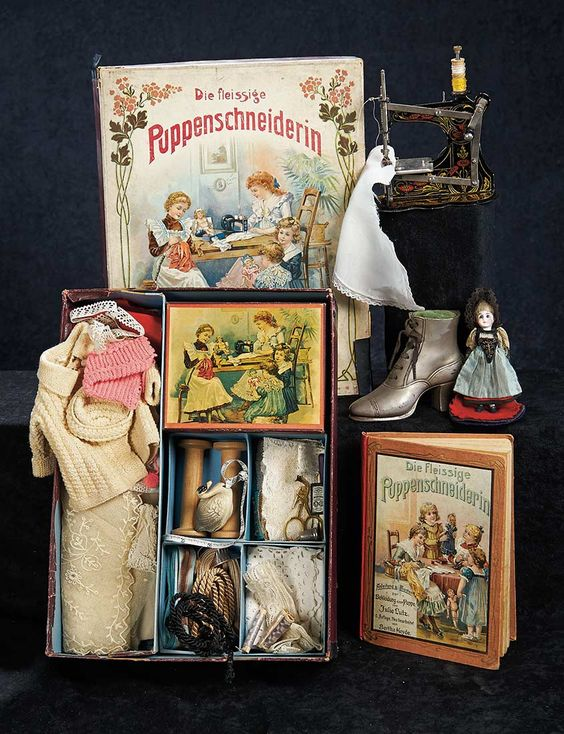 """German children's sewing box """"Die Fleissige Puppenschneiderin"""" (The Industrious Dolls-Dressmaker) with lithograph of children sewing for their dolls on the lid; toy sewing machine; """"Puppenmütterchens Nähschule"""" (Little-Doll-Mother's Sewing School) book with cover scene of children sewing for their dolls and containing patterns for doll costumes; a small bisque head doll in original folk costume on pincushion base; and a cast metal shoe pincushion. Germany, circa 1890."""