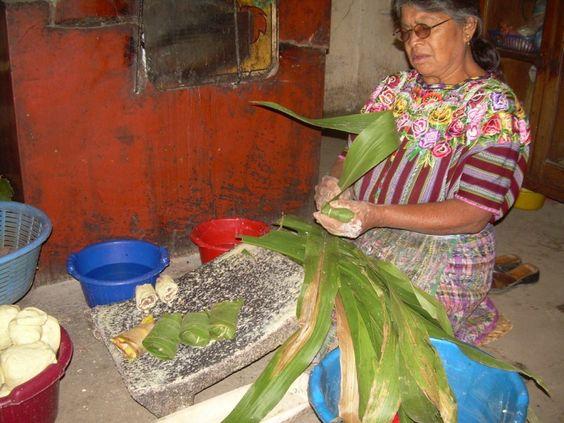 Mujer envolviendo tayuyos en hoja de milpa para vender en el mercado de Patzún
