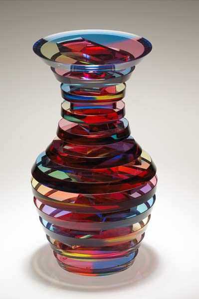 """SIDNEY HUTTER - Hutter has more than 25 years of experience making art out of glass. His craft begins with a sheet of plate glass which he and his staff spend hours hand cutting into specific shapes needed to create vases, sculptures, candleholders and other pieces of art. They dye and adhere the pieces together, and begin the process of cutting, grinding, and sanding until the final piece emerges."""""""
