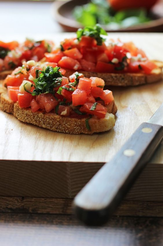 Un aperitivo saludable de las rebanadas de baguette a la parrilla frotado con ajo fresco y cubierto con tomates, ajo, albahaca y queso feta.