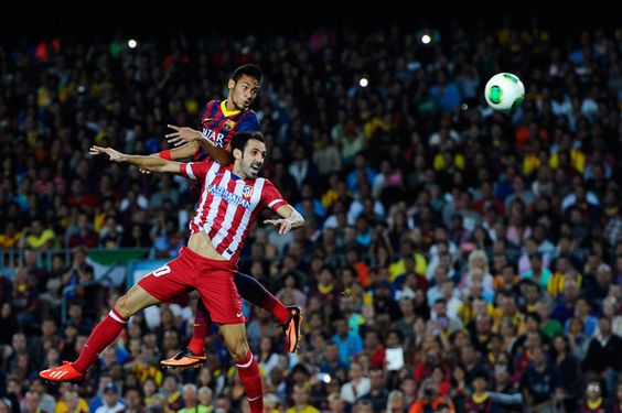 Neymar of FC Barcelona duels for a high ball with Juanfran of Atletico de Madrid during the Spanish Super Cup second leg match between FC Barcelona and Atletico de Madrid at Nou Camp on August 28, 2013 in Barcelona, Catalonia.