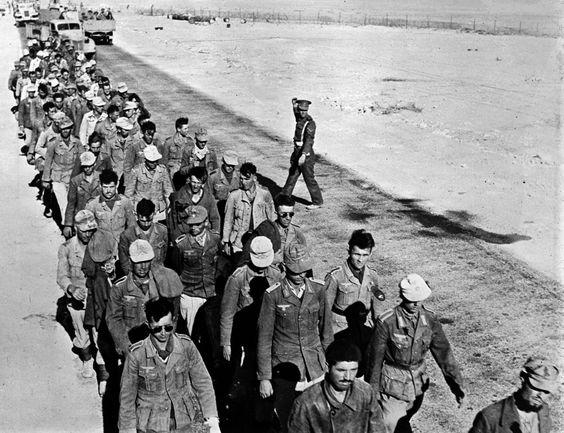 A British Lance Corporal guides a group of German prisoners taken during the Battle of El Alamein, 1942.