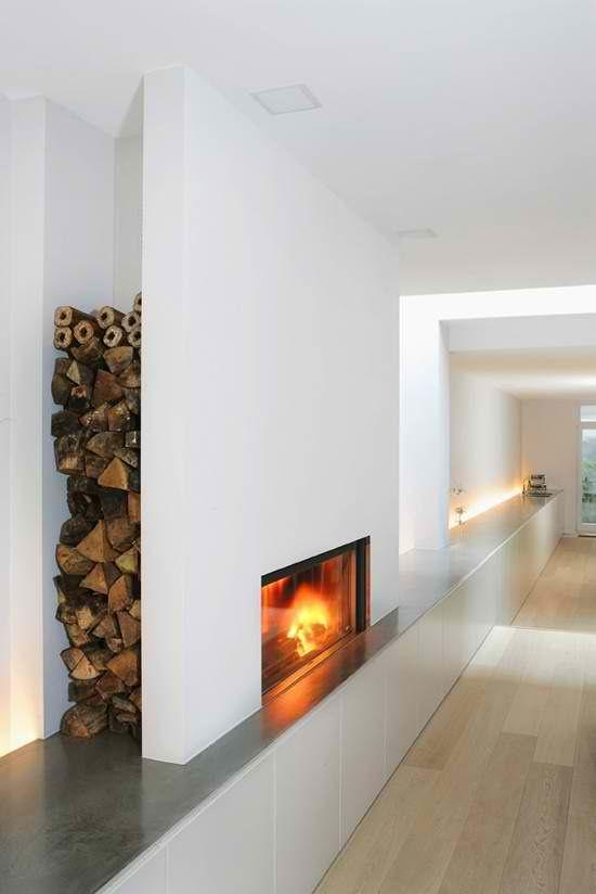 Modern fireplace with firewood log storage discreet alcove; storage below minimal steel hearth