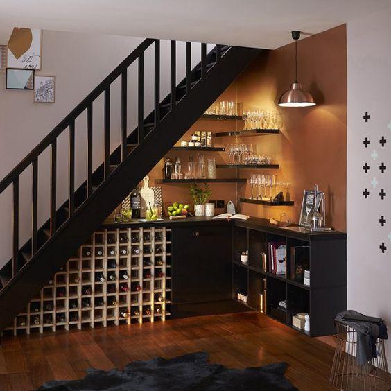 L'espace sous l'escalier offre de multiples possibilités qu'on ose rarement explorer. Un coin bureau, un espace rangement, un coin jeux pour les enfants... ou un véritable bar digne de ce nom aménagé en angle. Étagères au mur pour les verres, casiers en partie basse pour les bouteilles et le tour est joué !: