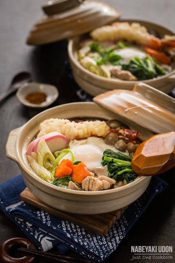 Nabeyaki Udon is a hot udon noodle soup traditionally served in individual donabe (earthernware pot) or iron pots. Nabeyaki Udon | Besides udon noodles, the soup usually includes chicken, kamaboko (fish cake), mushrooms, and vegetables such as spinach, Tokyo or naga negi, and carrot.  In addition, an egg and a large shrimp tempura is served on top.