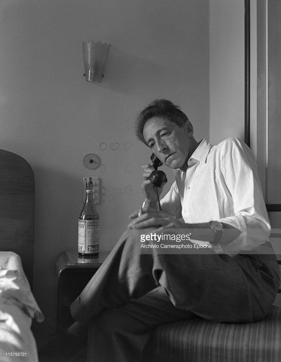 French writer Jean Cocteau portrayed while sitting on his bed, smoking a cigarette, wearing a white ciphered shirt and plaid trousers, talking on the telephone, a bottle of water on the night table, Paris, 1947.