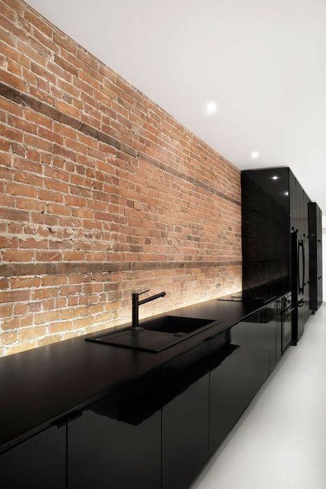 Une cuisine noir laqué, avec un éclairage indirect le long du plan de travail qui met en valeur la texture du mur en brique.