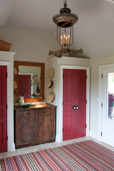 Stunning red doors and vintage chandelier in Sarah Richardson's modern farmhouse mud room. #vintagestyle #mudroom #farmhouse #Sarahrichardson