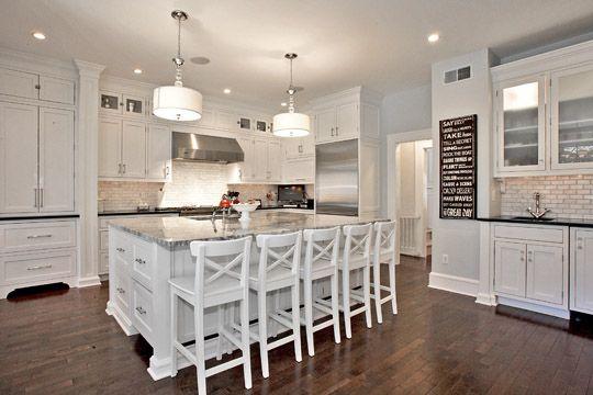 Custom cabinets in Benjamin Moore color, white granite on island and black honed granite on perimeter, and marble tile backsplash in 3 x 2 subway tile