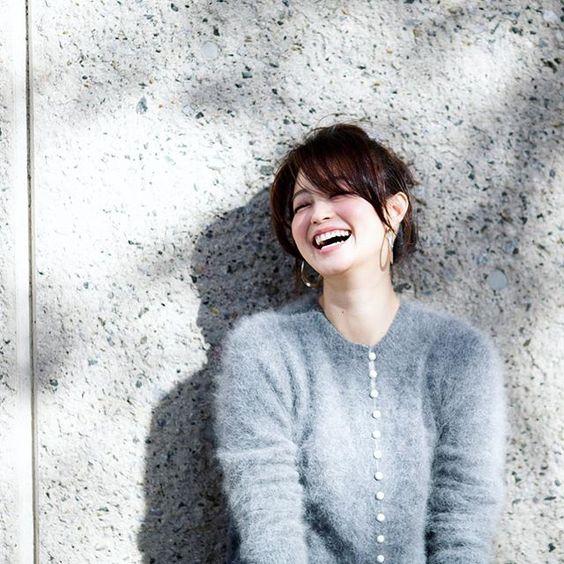 ふわふわのグレーのニットを着て笑っている小林涼子の画像