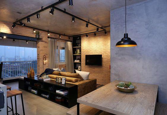 Decoração de apartamento pequeno. Parede de tijolinho, cimento queimado, prateleira com adornos, sofá bege. Mesa de madeira, pendente preto, luz natural.  #decoracao #decor #details #casadevalentina