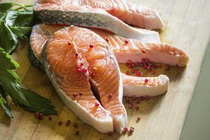 Fresh salmon steaks on a cutting board with red peppercorns and parsley.