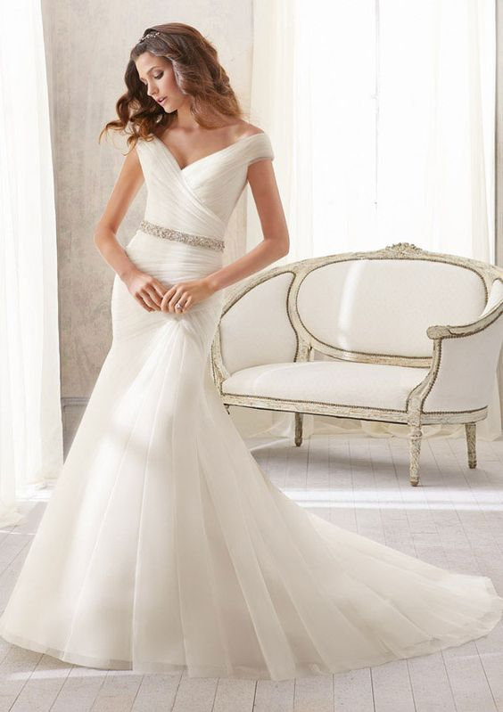 Asymmetrically Draped Soft Net allows this fishtail wedding dress to flatter the figure while the tip of shoulder straps balance the wide hemline. Shown with Crystal Beaded Organza Tie Sash to highlight a small waist.Sash also sold separately as Style 11054.