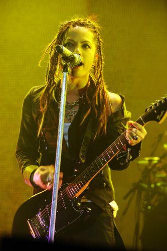 黄色いライトの中でギターを持って歌っているL'Arc〜en〜Ciel・hydeの画像