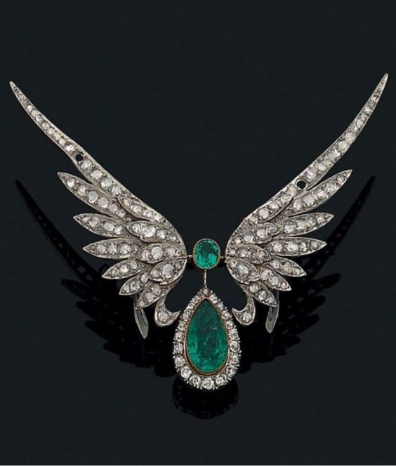 A Belle Epoque gold, emerald and diamond brooch, early 20th century. Designed as a pear-shaped emerald within a diamond-set frame, surmounted by a round emerald and flanked by a pair of wings set wtih rose-cut diamonds, mounted in 18k gold. #BelleÉpoque #brooch