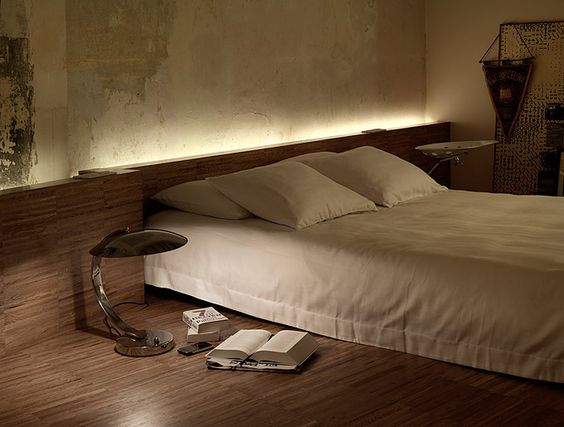 Low bed. Low slung headboard/box spanning wall. Slinky lighting. Off-white plush bed linens.