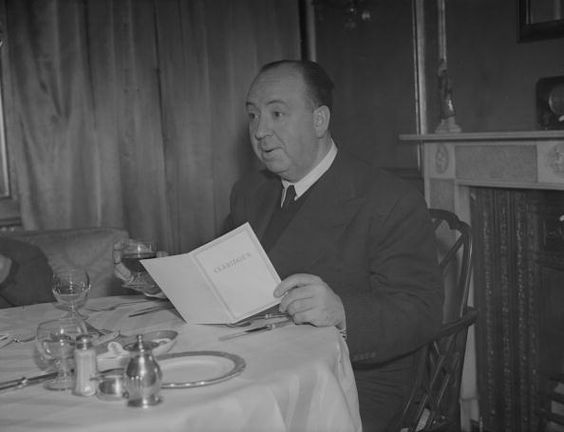 1943: British born film director and producer Alfred Hitchcock (1899 - 1980), drinking a glass of wine as he reads the menu at Claridges in London. (Photo by Express/Express/Getty Images)