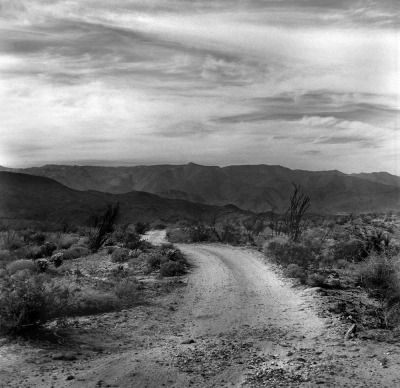 Desert road near Borrego Springs, San Diego County, California, Santa Rosa Mtns. in the background. Photographed 1987 by Dave Glass