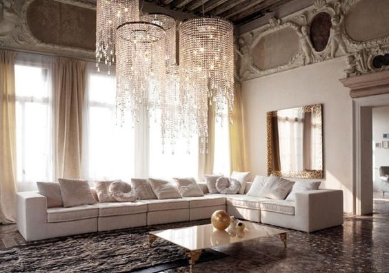 A stunning living room, and is actually one of the most luxurious and glamorous living rooms that I've seen. The focal point is represented by an imposing cascading crystal chandelier that adds character, sophistication, and illuminati to the living room.