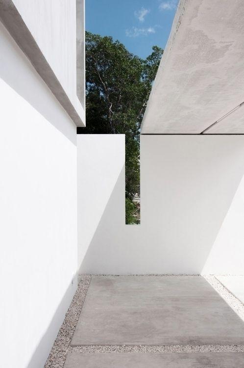 Carport with concrete pavers and gravel. Casa Garcias by Warm Architects.