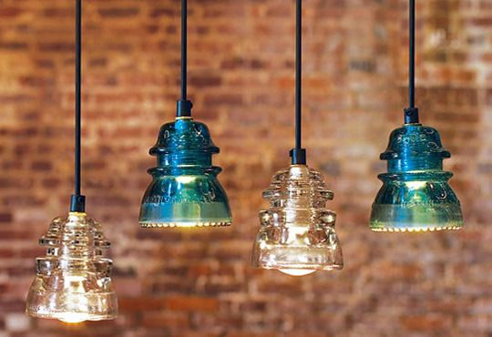 Vintage telegraph insulators that have been converted into hanging pendant lights.