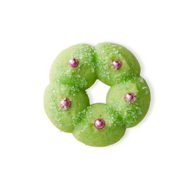 Spritz cookies: Retro wreath    Make Basic Spritz Cookies recipe. Tint master spritz dough a pale green using paste or gel food coloring. Press dough through a cookie press fitted with a wreath-shaped cookie plate directly onto baking sheets; decorate with pink dragées. Bake and cool as directed. Makes 72 cookies.
