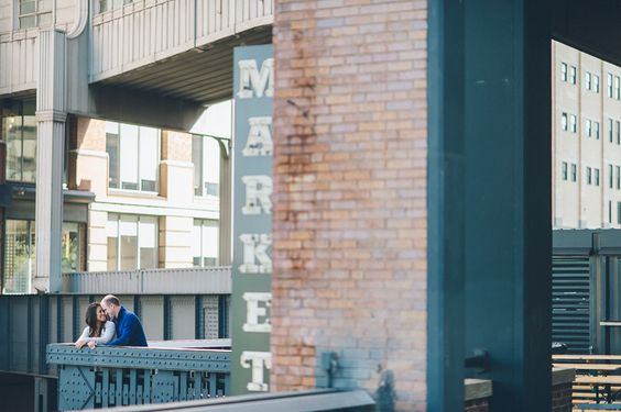 A couple lean over a railing at High Line Park during their engagement session with NYC wedding photographer Ben Lau.
