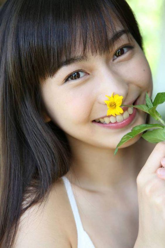 白いビキニを着て黄色い小さな花を持っている植村あかりの画像