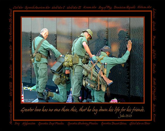 """Vietnam veterans standing at a memorial wall. Scripture quoted """"Greater love has no one other than this, that he lay down his life for his friends."""" All US wars and conflicts are listed around the border of the photograph. Image © Carolyn Marshall, www.carolynmarshallphotography.com."""
