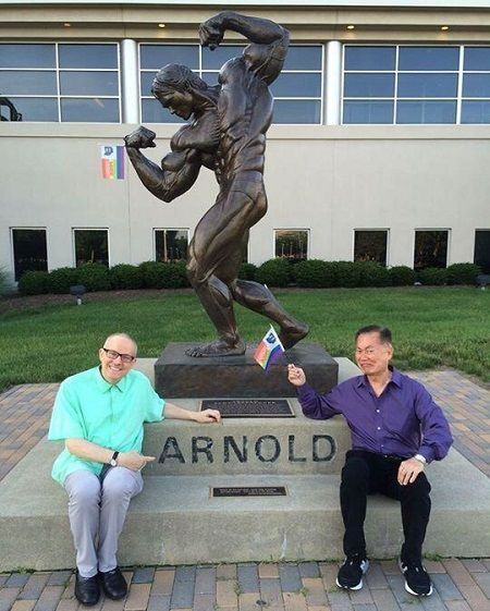 "George and Brad at an Arnold Schwarzenegger statue in Columbus, Ohio. When Schwarzenegger vetoed California's marriage equality bill, it helped George decide to come out.  ""That night, we saw all these young people pouring out onto Santa Monica Boulevard, venting their rage against Schwarzenegger. They inspired me. I'd spent a lifetime being silent on the issue… now I had to speak up."""