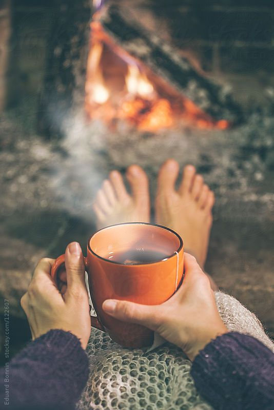 Woman relaxing with cup of tea in front fireplace. by BONNINSTUDIO for Stocksy United