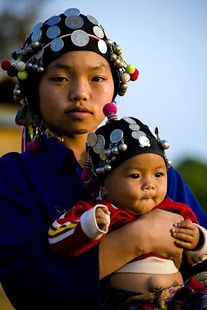 Asia | Portrait of a young Mother carrying her child wearing traditional clothes and headdress, Luang Namtha, Laos