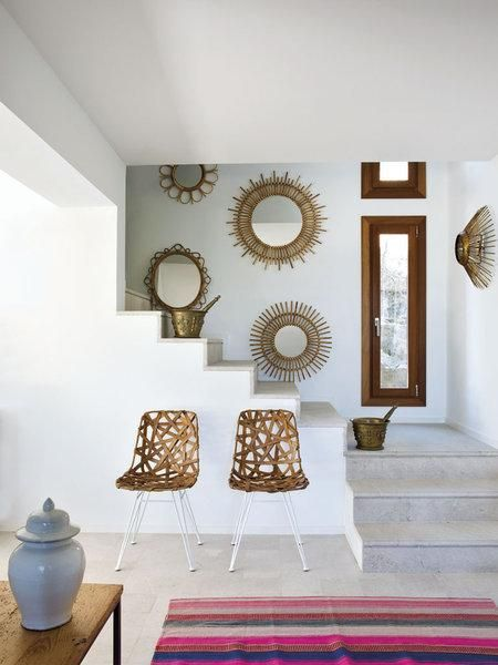 An array of sunburst mirrors and a pair of wrapped rattan chairs combine for an eye-catching composition against this Mallorcan home's crisp white walls.: