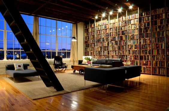 A bookshelf wall in a loft in Birmingham, Alabama.  Don't like the furniture and staircase style, but love the books.