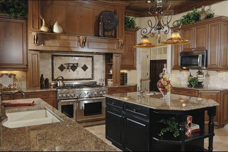 These cabinets combine a medium to dark tone wood with black in the center and all of it really compliments the darker granite. You get a more formal looking room, but nice at the same time.