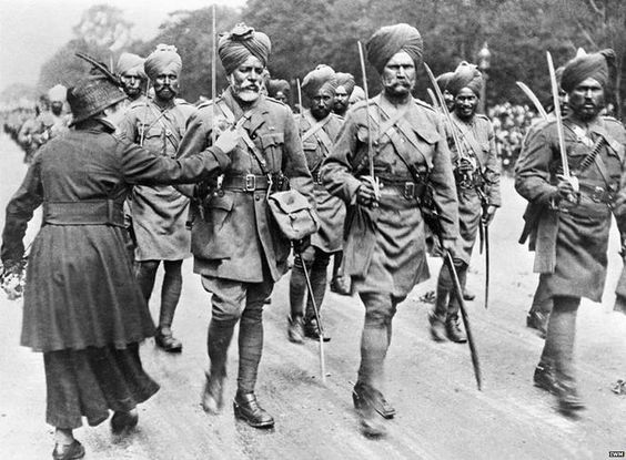 During a march past of Indian troops, a woman pins flowers on to the tunic of one of the soldiers.