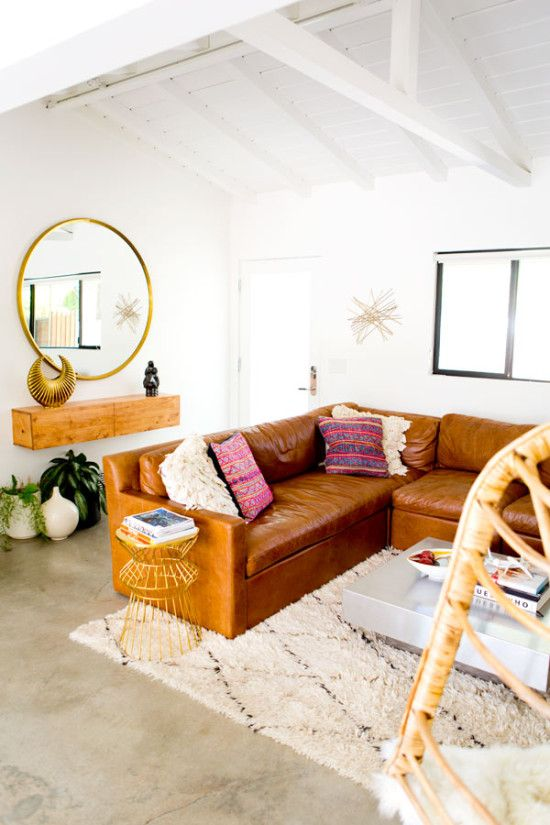 Caramel leather sofa, plush ivory rug, concrete floors, floating cabinet and gold accents make this living room feel fresh, funky and cozy all at once.