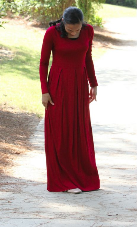A modest womens long sleeve maxi dress with an elastic waist, side pockets and a…