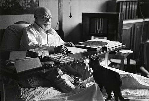 Henri Matisse in his apartment at the Hotel Regina in Nice, photographed by Robert Capa (August 1949). (EEEEE LOOK HOW CUTE HE IS WITH HIS BEARD AND HIS BOOKS AND HE HAS A CAT)